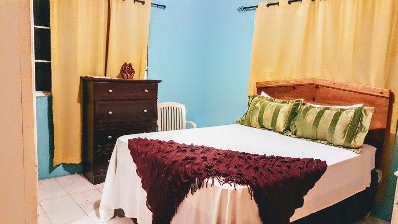 Quarto principal com cama queen-size e outro mobiliário para tornar a sua estadia confortável.