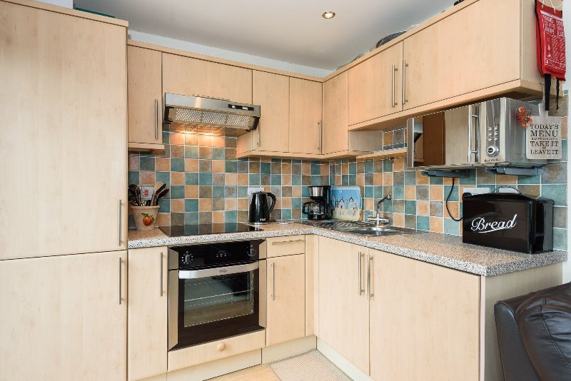 Fully fitted kitchen with electric oven, ceramic hob, fridge freezer, microwave, kettle, toaster