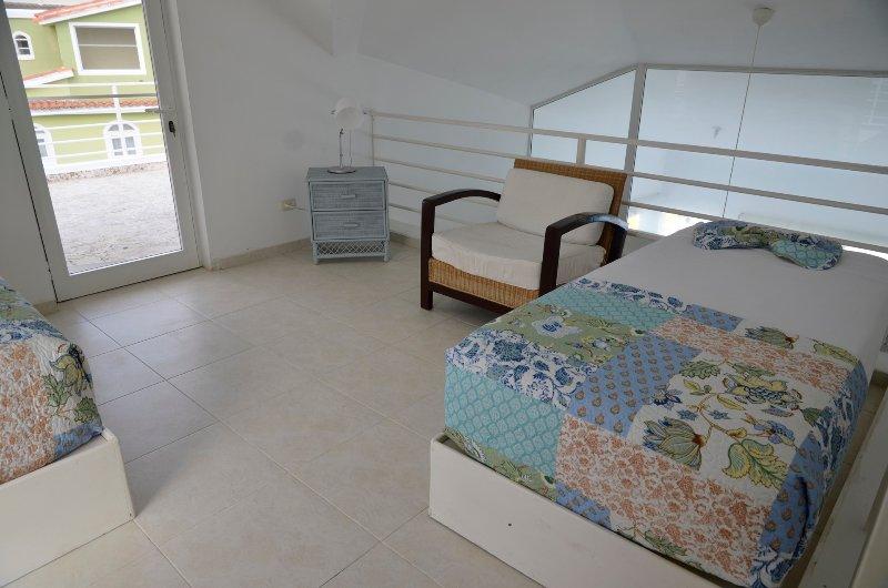 Entrepiso con 2 camas individuales y acceso a la terraza de la azotea