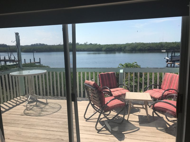 cubierta de vista de las puertas corredizas de vidrio enorme vista frente al río. sillas del patio, parrilla