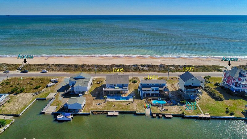 Air view of property and neighbors.. Beach is across street and pool and canal in backi.