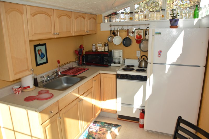 Kitchen with stove, fridge, microwave, coffee maker, toaster, dishes, pots/pans, etc.