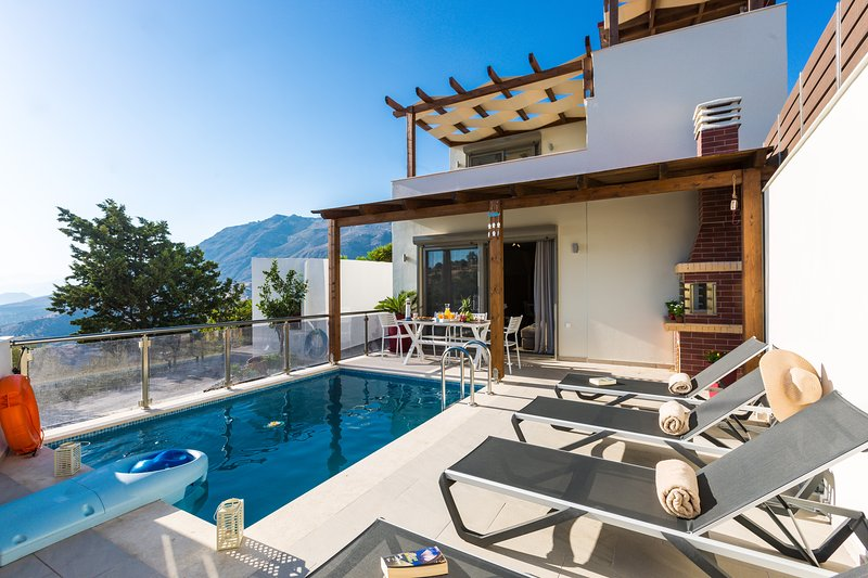 Outdoor area of our villa with pool, sun beds, umbrella, barbecue & dining area