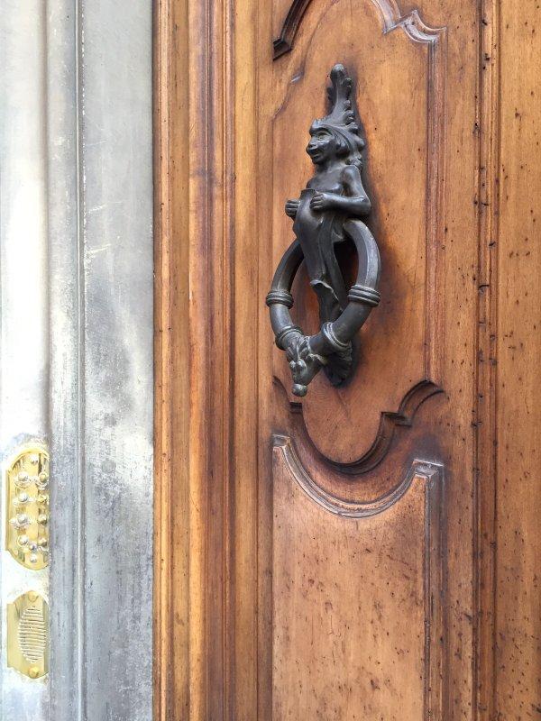 Doorknocker of the street door. The historic building dates back to the 19th century