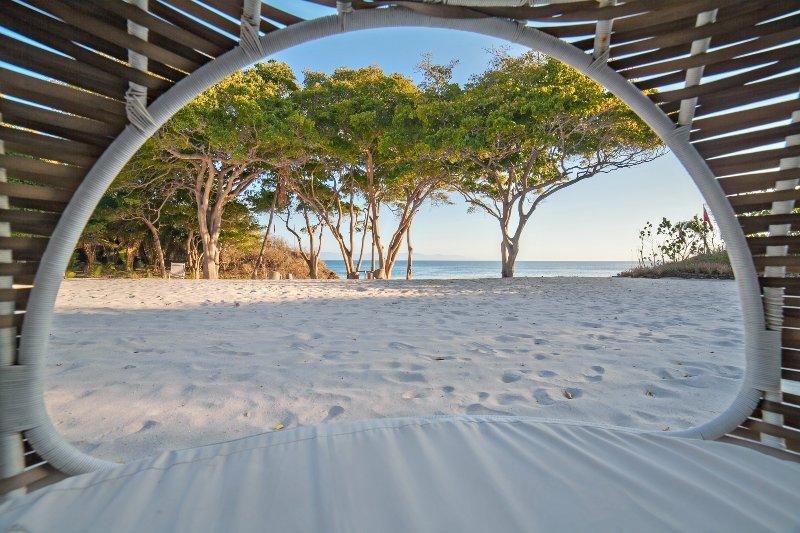 Vista desde el interior de una de las tumbonas de playa con techo en la arena
