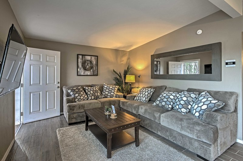 The living room features plush sofas and a flat-screen Smart TV.