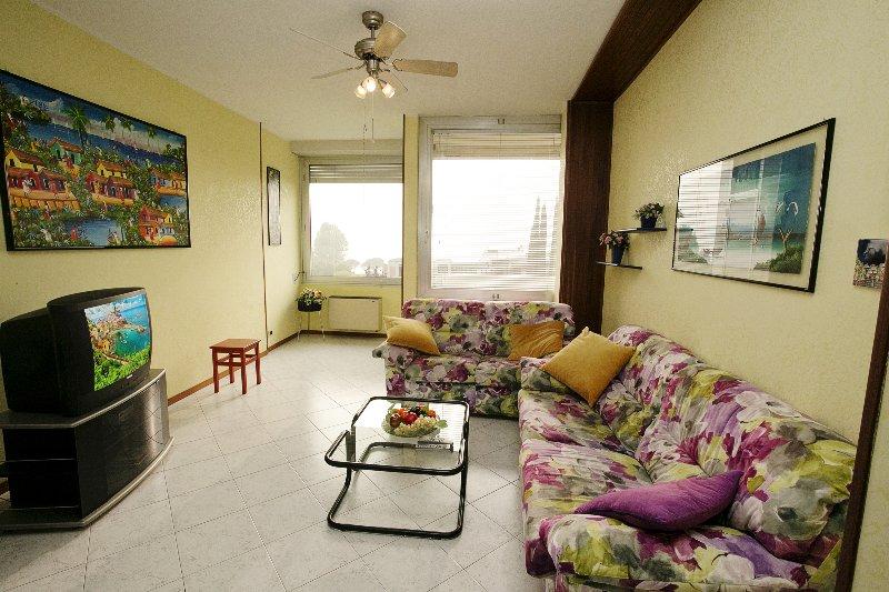 Spacious living room wih a comfortable sofa and view of the lake