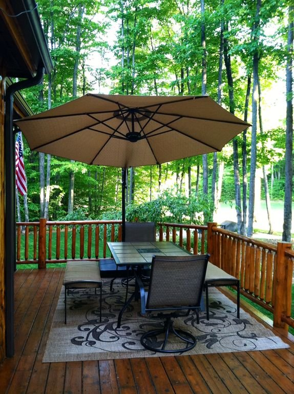 The back deck includes a gas grill and table for outdoor dining.