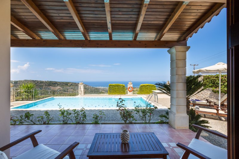 Sitting area sotto un pergolato accanto alla piscina con vista sul mare