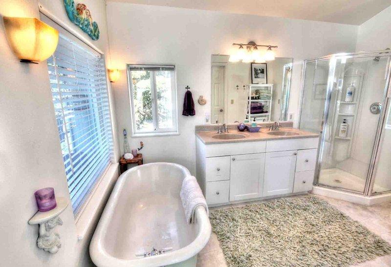 O banheiro principal em anexo tem pias duplas e uma banheira com pés, chuveiro.