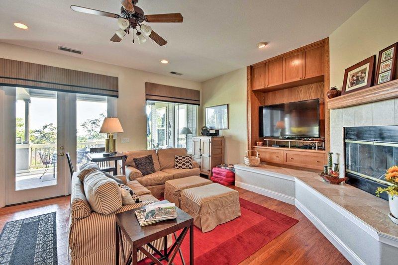 La salle de séjour est rempli de lumière naturelle et dispose d'une cheminée au feu de bois.