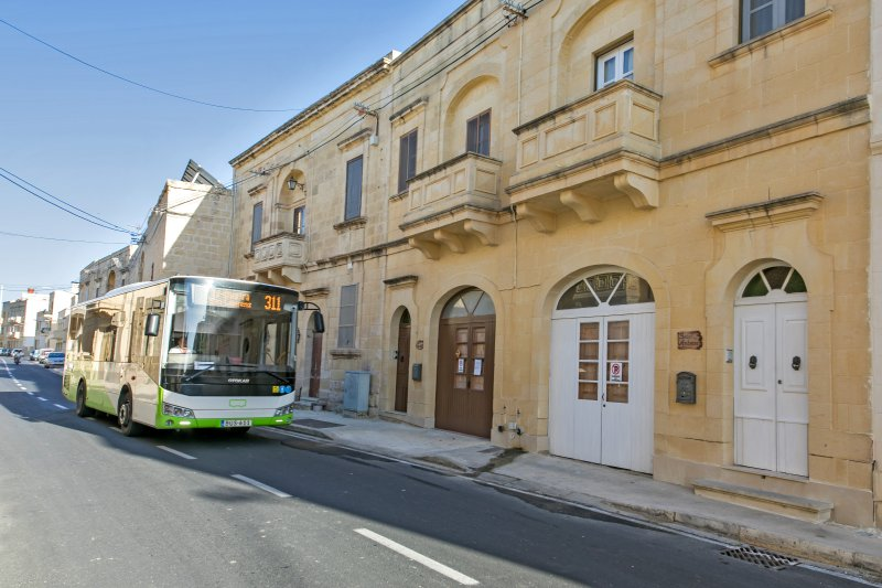 Property has white painted doors and windows. The bus 311 is a frequent route in San Lawrenz