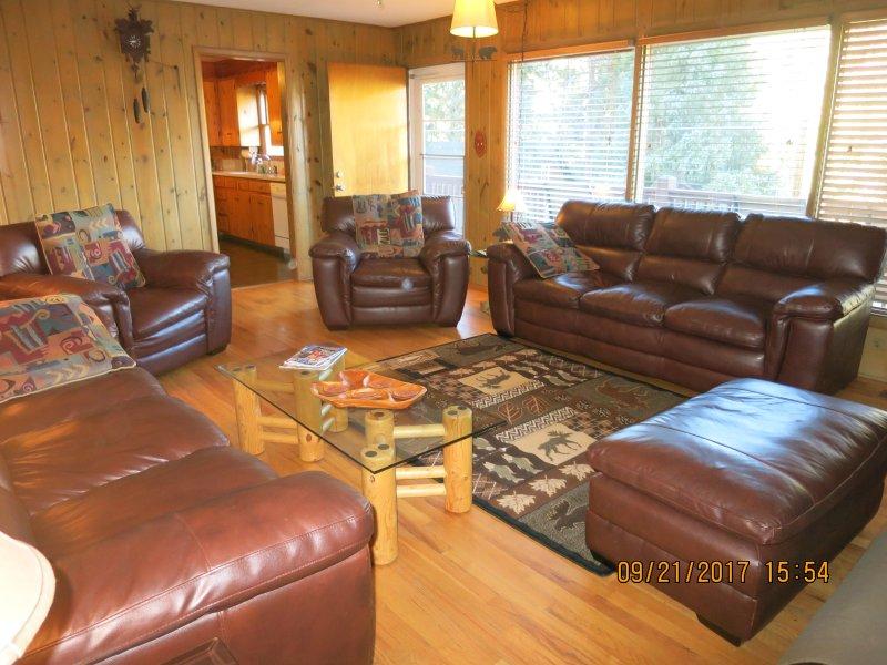 Amplia sala de estar tiene 2 juegos de muebles de cuero