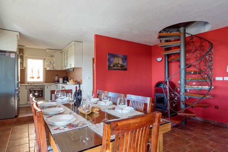 Zona pranzo e soggiorno con cucina completamente attrezzata, camino e vista incredibile a Spalato