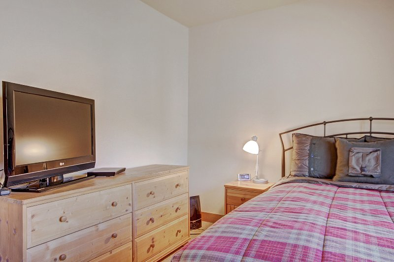 Guest Bedroom - This room features a queen-sized bed and a flat-screen TV.
