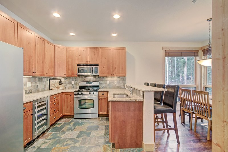 Kitchen and Dining Area - The kitchen features granite counter-tops and stainless steel appliances.