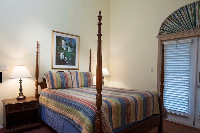 Master bedroom has its own full bath and doors to elevated patio overlooking the pool.