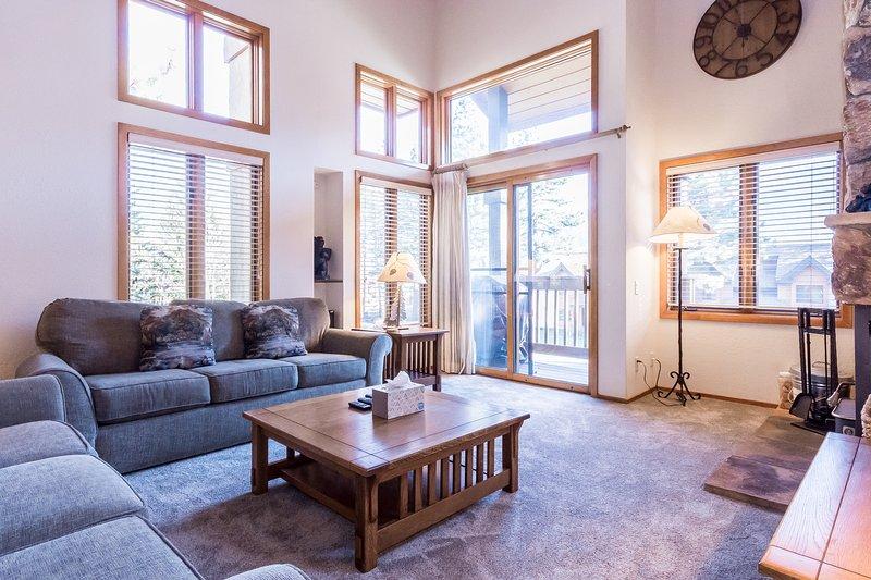 Sala de estar con chimenea de leña, televisión de pantalla plana y terraza.
