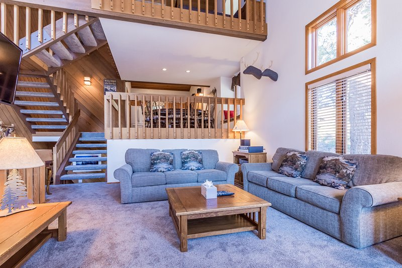 Living Room with wood burning fireplace, flat screen tv and deck.