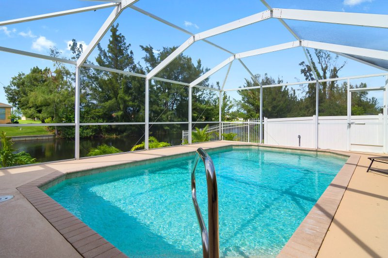 Waterfront, private fenced in backyard with sparkling heated swimming pool