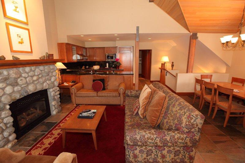 Rilassati e rilassati nell'ampio soggiorno, completo di divani e caminetto in pietra.