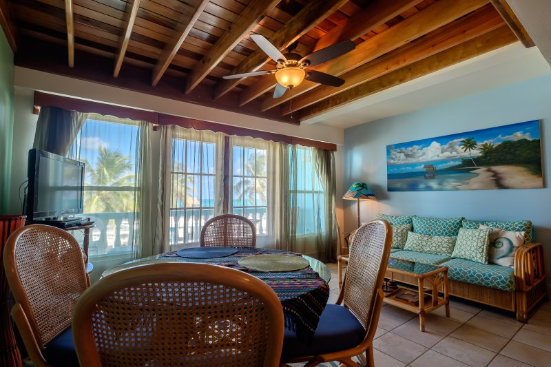 Gorgeous colorful, bright living room with balcony overlooking the turqoise water of the Caribbean!