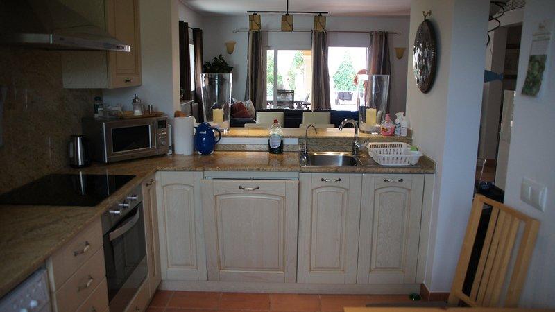 Küche mit Blick ins Wohnzimmer und Pool