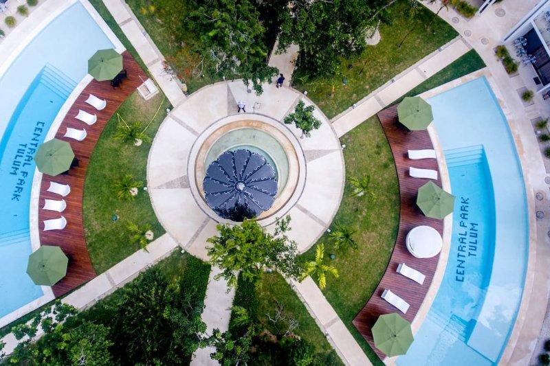 El patio del complejo cuenta con plantas tropicales, junto a dos piscinas y áreas de descanso atractivos.