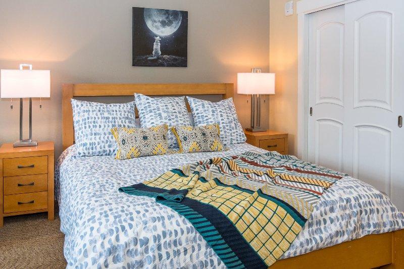 Cama King con acogedora ropa de cama nueva