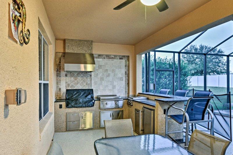 Enjoy preparing meals in the outdoor kitchen overlooking the pool.