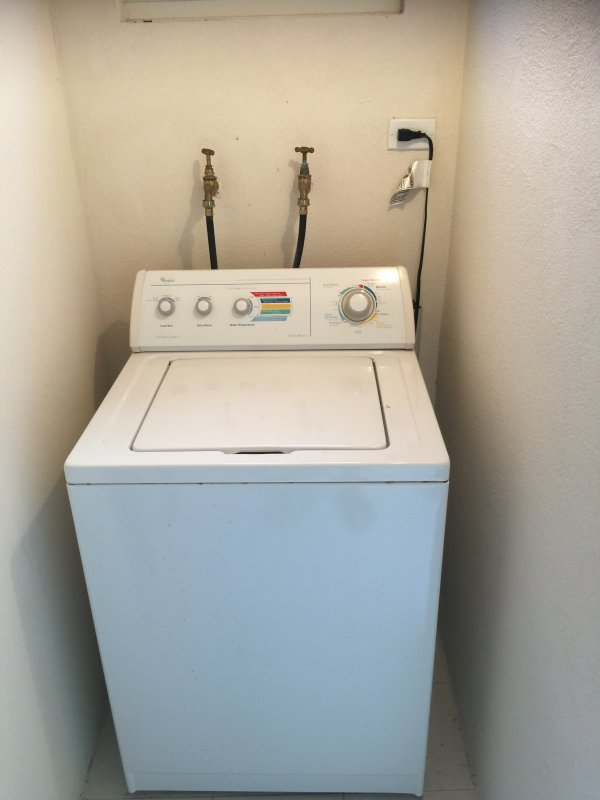 American top loading easing machine in separate laundry room