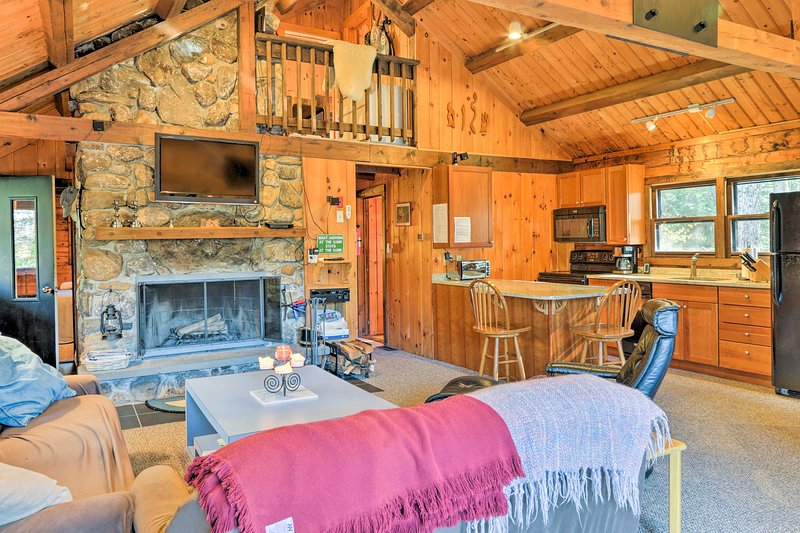 The great living area boasts plush sofas, a flat-screen TV,  and a wood-burning fireplace for a cozy night in with loved ones.