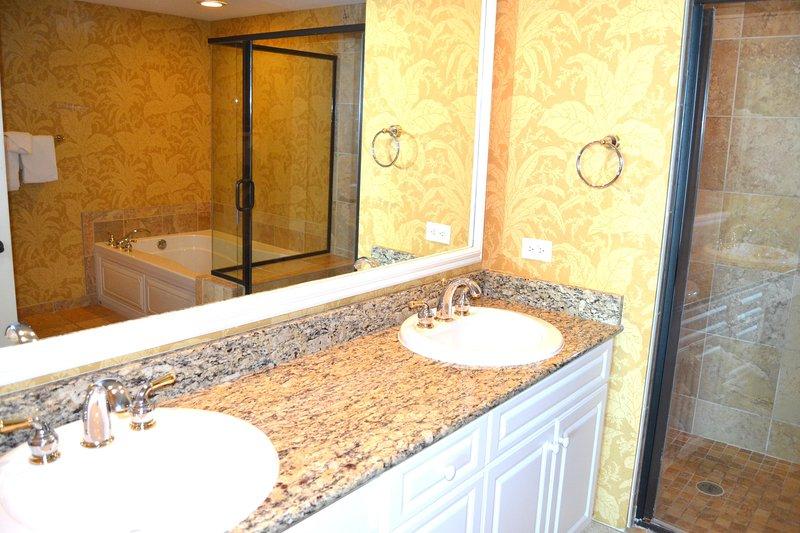 Baño principal, dos lavabos, encimera de granito, baldosas de cerámica, plato de ducha