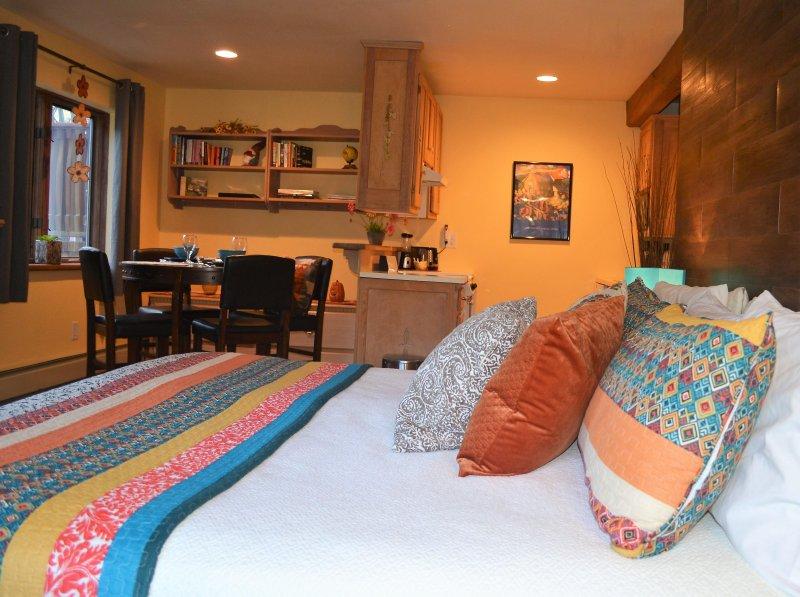 área de dormitorio con comedor y área de cocina