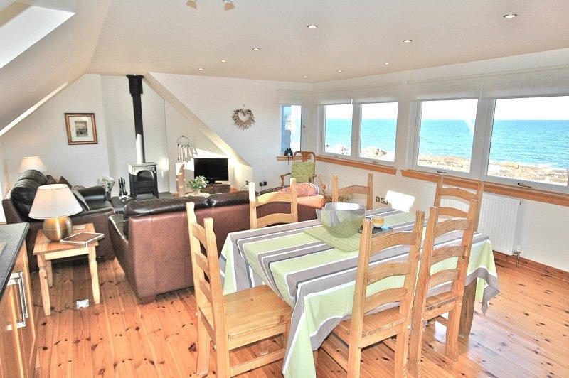 Abrir plano de sala de estar / jantar / cozinha com vista para o mar.