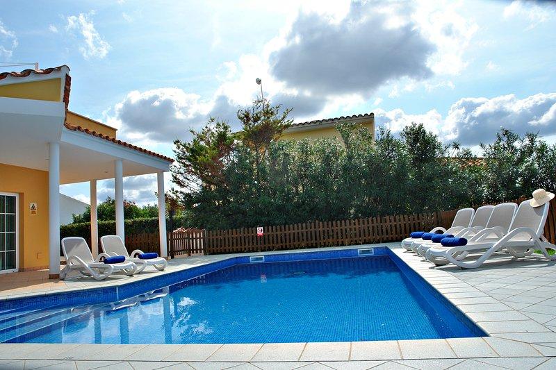 Gran piscina privada con solarium y mobiliario exterior