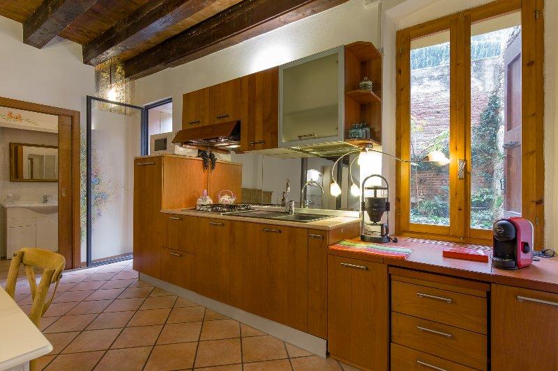 A cozinha com um grande frigorífico, microondas, máquina de lavar louça, alemão e máquinas de café italianos