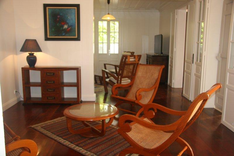 De 2 traditionella vardagsrum med Creole sockerrör fåtöljer.