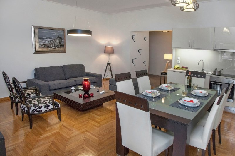The living room with the open plan kitchen and the dining table