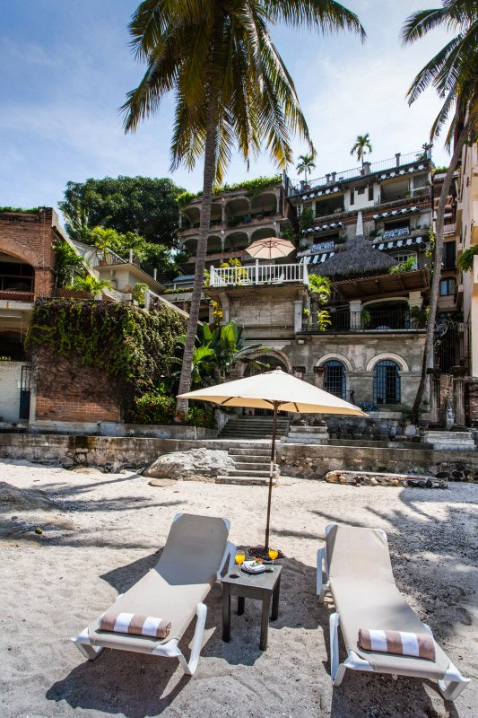Beach loungers with Casa Tres Vidas in the background and sister property Quinta Maria Cortez