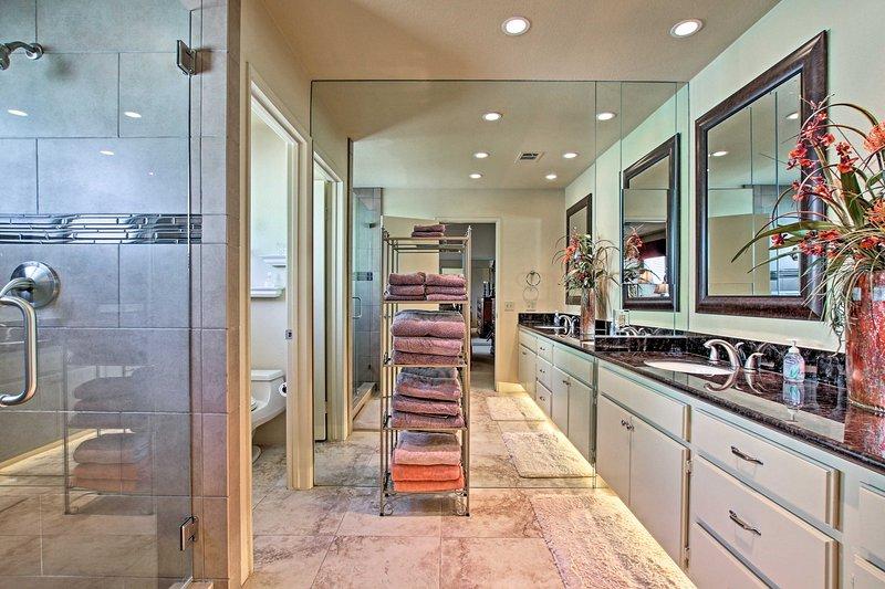 Encuentra toallas, una cabina de ducha y doble lavabo en el baño.