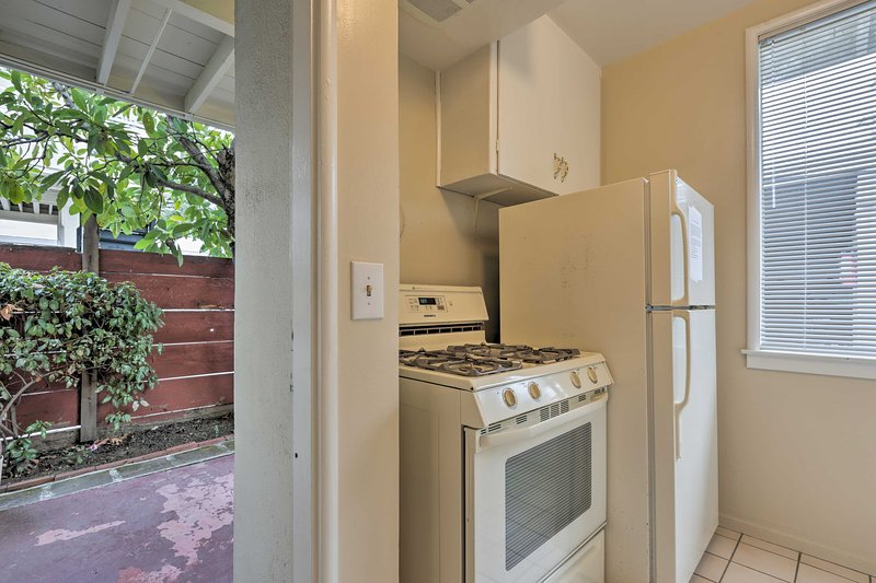 The fully equipped kitchen has a full-sized fridge and 4-burner gas stove.