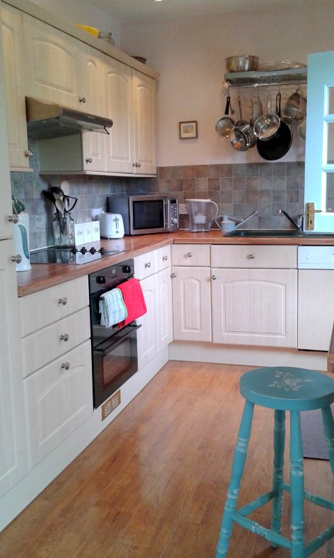 Well equipped kitchen leading onto pretty decked area outside