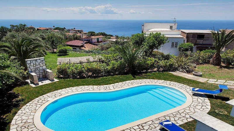 piscina privada, jardín, solarium y vistas parciales al mar en villa Sorrento Aldo reserva de alquiler de dejar