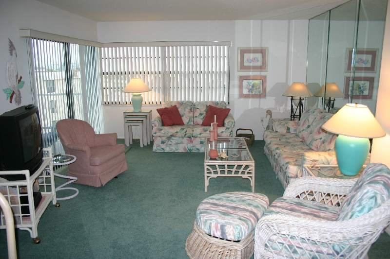 Ocean view living room with a sofa sleeper, love seat, cozy chair, TV and VCR.