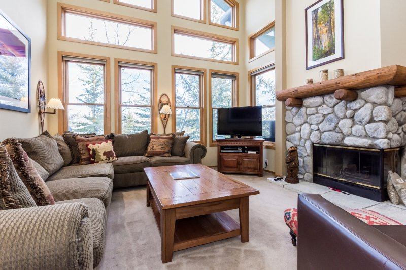 Living room with fireplace, flat screen TV and private outdoor patio.
