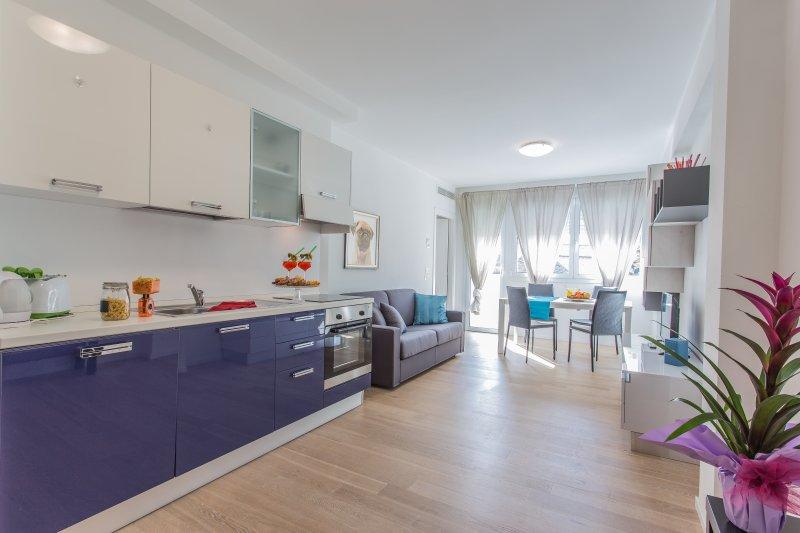 Sala ampla com cozinha, sofá-cama, mesa de jantar e terraço