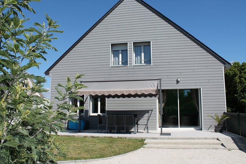 Façade de la maison, salon de jardin, barbecue et store