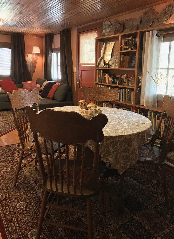 Salón con sofá cama, biblioteca y comedor