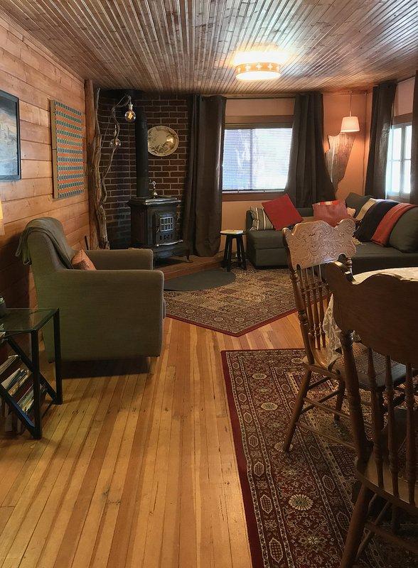 sala de estar con estufa de leña, sofá cama y zona de comedor